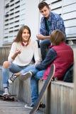Tres adolescentes que cuelgan hacia fuera al aire libre Foto de archivo libre de regalías