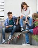 Tres adolescentes que cuelgan hacia fuera al aire libre Foto de archivo