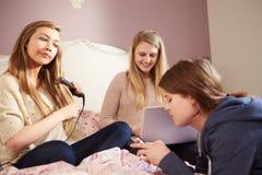 Tres adolescentes que se relajan en dormitorio junto Foto de archivo libre de regalías
