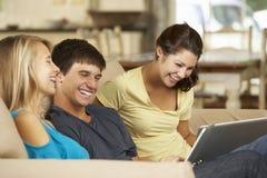 Tres adolescentes que se sientan en el ordenador y el ordenador portátil de Sofa At Home Using Tablet Imagenes de archivo