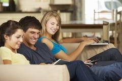 Tres adolescentes que se sientan en el teléfono, la tableta y el ordenador portátil de Sofa At Home Using Mobile Imagenes de archivo