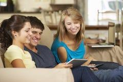 Tres adolescentes que se sientan en el teléfono, la tableta y el ordenador portátil de Sofa At Home Using Mobile Imagen de archivo libre de regalías