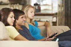Tres adolescentes que se sientan en los teléfonos móviles de Sofa At Home Texting On Imagenes de archivo