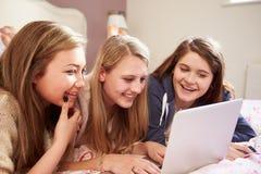 Tres adolescentes que usan el ordenador portátil en dormitorio Foto de archivo