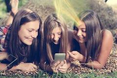 Tres adolescentes que usan el teléfono al aire libre Foto de archivo libre de regalías