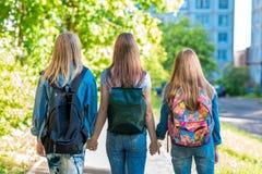 Tres adolescentes Se detienen las manos del ` s Las devoluciones se dirigen después de escuela Verano en naturaleza Detrás de las Imagen de archivo libre de regalías