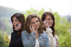 Tres adolescentes sonrientes con los teléfonos celulares Fotografía de archivo libre de regalías