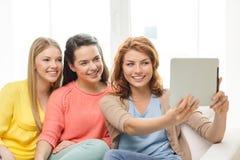 Tres adolescentes sonrientes con PC de la tableta en casa Fotografía de archivo