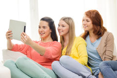 Tres adolescentes sonrientes con PC de la tableta en casa Foto de archivo libre de regalías