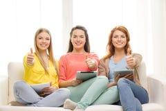 Tres adolescentes sonrientes con PC de la tableta en casa Imagenes de archivo