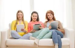 Tres adolescentes sonrientes con PC de la tableta en casa Imagen de archivo libre de regalías