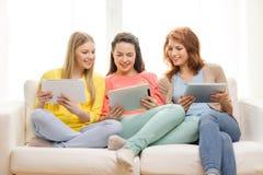 Tres adolescentes sonrientes con PC de la tableta en casa Fotos de archivo