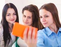 Tres adolescentes sonrientes que toman el selfie con la cámara del smartphone Fotos de archivo