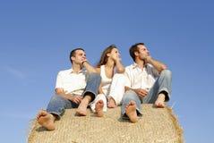 Tres adultos jovenes en una bala de la paja Imagen de archivo libre de regalías