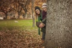 Tres adultos jovenes puestos dirigen hacia fuera detrás de un árbol Piso por completo del pasto Imagen de archivo libre de regalías