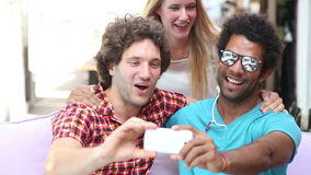 Tres adultos jovenes que se divierten que toma selfies espontáneos almacen de video