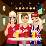 Tres aficionados al fútbol ingleses felices que beben la cerveza en el pub Foto de archivo