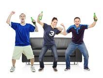 Tres aficionados deportivos que celebran Foto de archivo libre de regalías