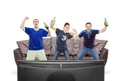 Tres aficionados deportivos que ven la TV Fotos de archivo libres de regalías