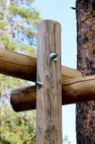 Tres agrietaron el registro de madera sujetado con el nuevo perno brillante con dos nueces Fotografía de archivo libre de regalías