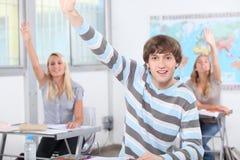 Alumnos con los brazos aumentados Imagen de archivo libre de regalías