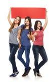 Tres amigas con la bandera roja Imágenes de archivo libres de regalías