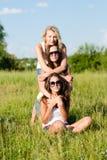 Tres amigas felices de las mujeres jovenes que abrazan contra el cielo azul Imagen de archivo libre de regalías