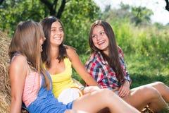 Tres amigas que se divierten en pila del heno Imagen de archivo libre de regalías