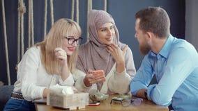 Tres amigos étnicos multi hombre y mujeres están mirando en smartphone en café almacen de metraje de vídeo
