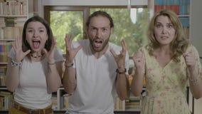 Tres amigos adolescentes en choque y pánico que gritan horrorizando la expresión facial que ven algo asustadizo - metrajes