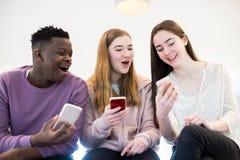 Tres amigos adolescentes que r?en como comparten el contenido en los tel?fonos m?viles imagen de archivo libre de regalías