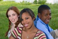 Tres amigos adolescentes que se sientan en la hierba Foto de archivo