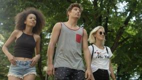 Tres amigos adultos jovenes que dan un paseo en parque Fotos de archivo libres de regalías