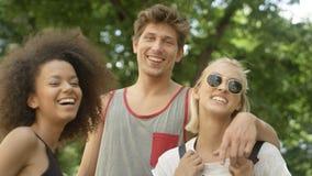 Tres amigos adultos jovenes que dan un paseo en parque Imagenes de archivo