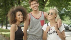 Tres amigos adultos jovenes que se divierten en un parque de la ciudad Fotos de archivo libres de regalías