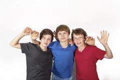 Tres amigos alegres felices en azul, rojo y negro fotos de archivo