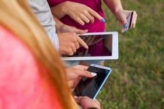 Tres amigos con el artilugio electrónico en parque Cierre para arriba Foto de archivo libre de regalías