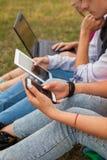 Tres amigos con el artilugio electrónico en parque Cierre para arriba Fotos de archivo libres de regalías