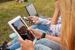 Tres amigos con el artilugio electrónico en parque Cierre para arriba Imagen de archivo libre de regalías