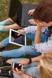 Tres amigos con el artilugio electrónico en parque Cierre para arriba Imagenes de archivo