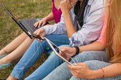 Tres amigos con el artilugio electrónico en parque Cierre para arriba Fotografía de archivo libre de regalías