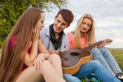 Tres amigos con la guitarra que se sienta en la manta en el parque Imagen de archivo