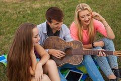 Tres amigos con la guitarra que se sienta en la manta en el parque Imagenes de archivo