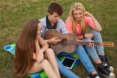 Tres amigos con la guitarra que se sienta en la manta en el parque Fotos de archivo
