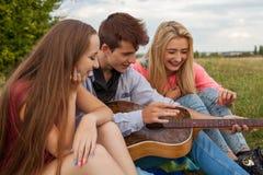 Tres amigos con la guitarra que se sienta en la manta en el parque Fotos de archivo libres de regalías