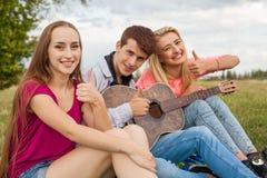 Tres amigos con la guitarra que se sienta en la manta en el parque Imagen de archivo libre de regalías