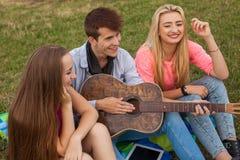 Tres amigos con la guitarra que se sienta en la manta en el parque Fotografía de archivo libre de regalías
