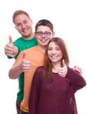 Tres amigos con los tumbs suben y sonríen imagen de archivo