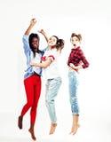 Tres amigos de adolescente diversos bastante jovenes de las naciones que saltan la sonrisa feliz en el fondo blanco, gente de la  Imágenes de archivo libres de regalías