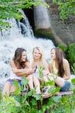 Tres amigos de adolescente que se divierten cerca de la cascada el día de verano al aire libre Foto de archivo